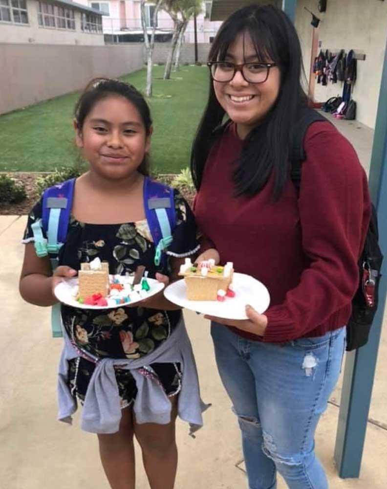 High school volunteer Esmeralda with her mentee Gladis