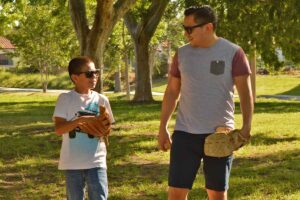 A male volunteer in Orange County plays catch with his mentee.