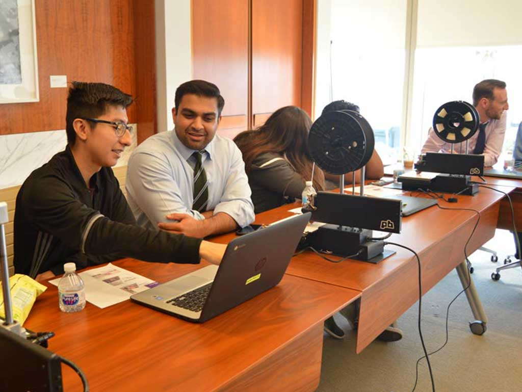 Corporate employees mentor high school students at their workplace